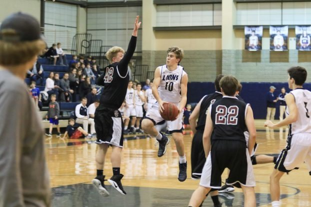 Briarwood's Michael Hiers avoids the contact as he lays the ball in for two of his team-high 17 points.